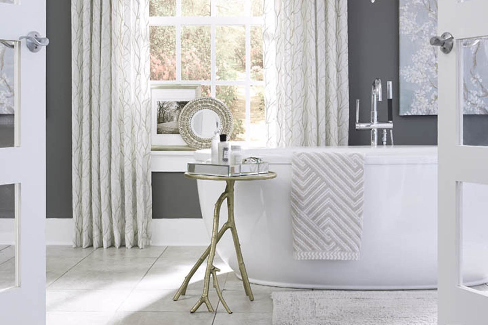 top interior designer designs master bathroom remodel with grey and white accents and a large bathtub