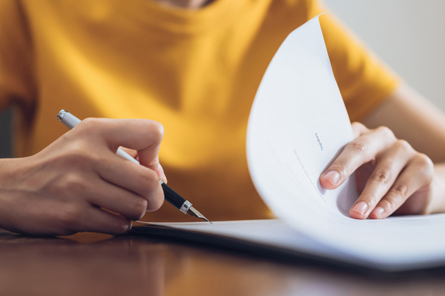 Woman signing document and hand holding pen putting signature at paper, order to authorize their rights for interior designer