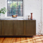 vintage living room dresser with exposed brick walls and minimalistic decorations