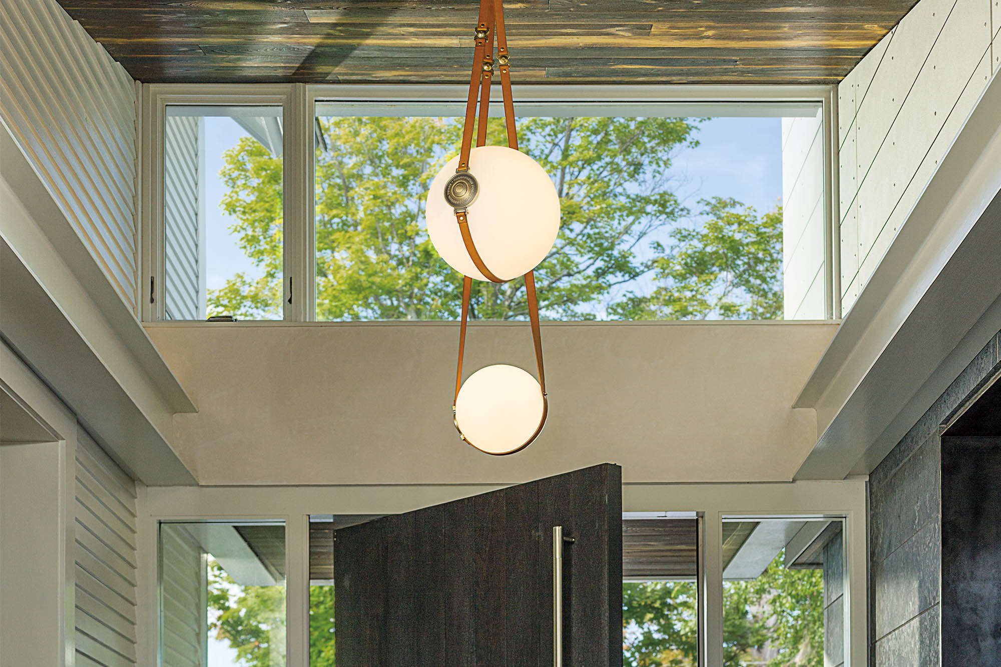 chandelier hanging in entranceway of a house with big windows