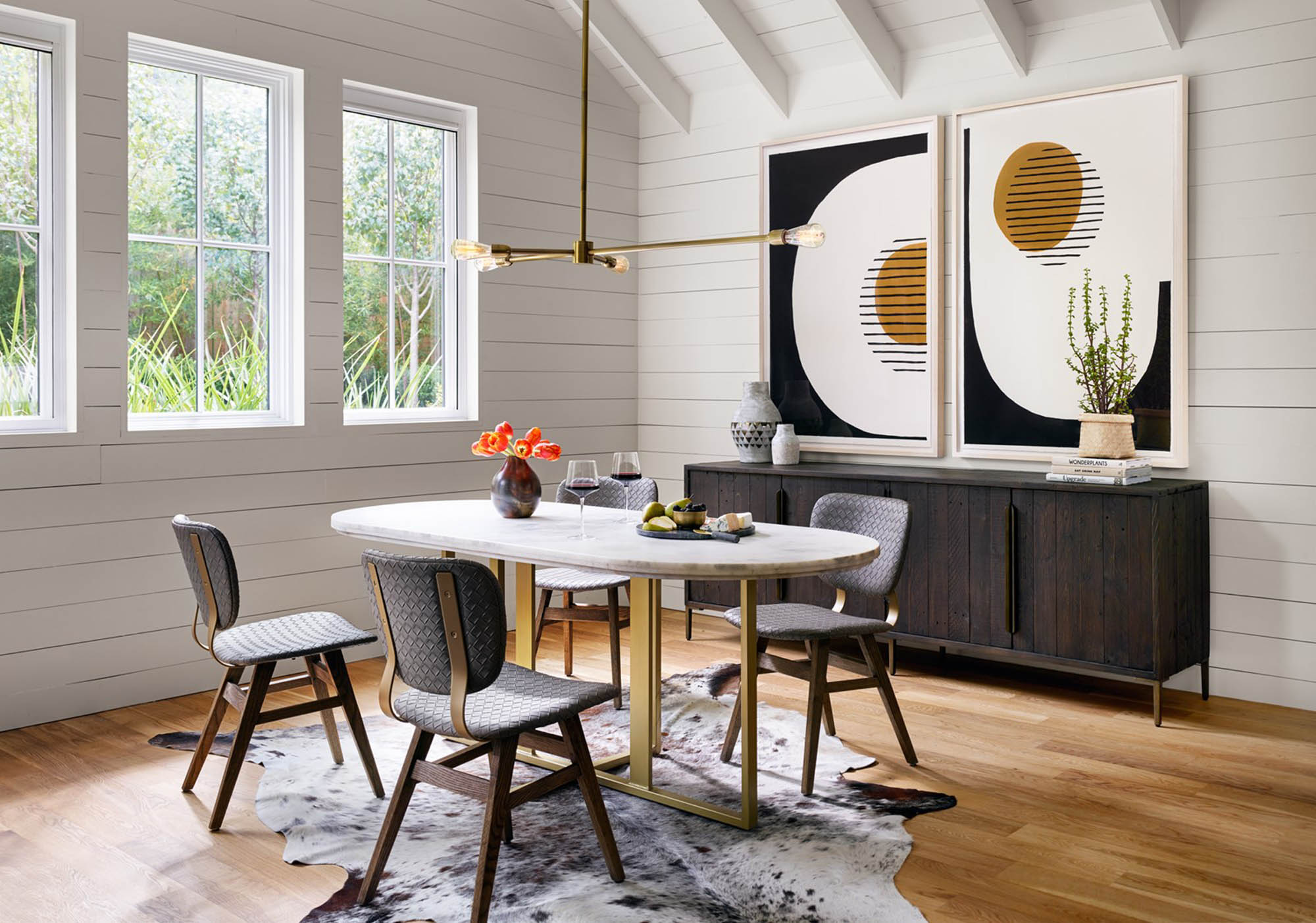 top interior designer designs modern dining room with small table and gold accents